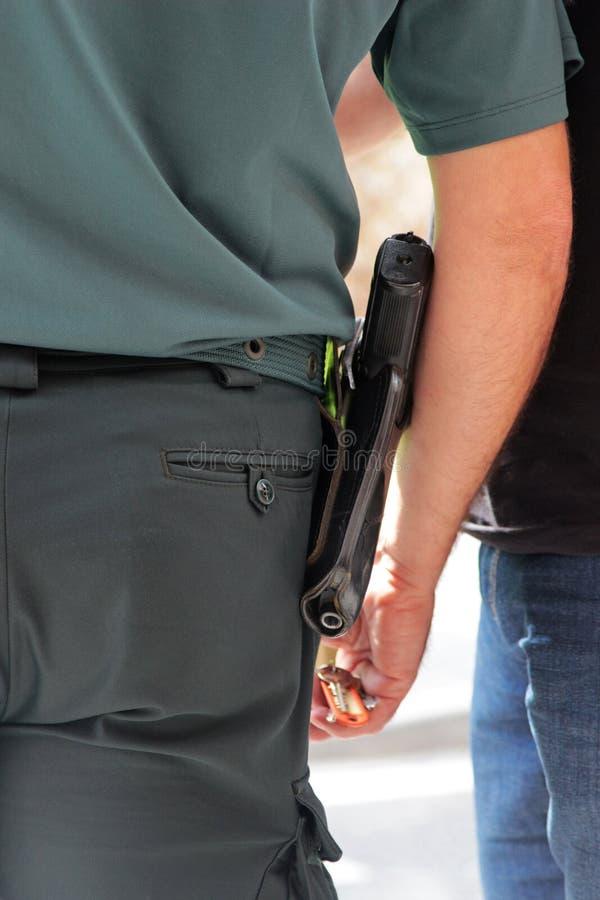 Αστυνομικός που φορά ένα πιστόλι σε μια πιστολιοθήκη ζωνών, οπισθοσκόπο στοκ φωτογραφία με δικαίωμα ελεύθερης χρήσης