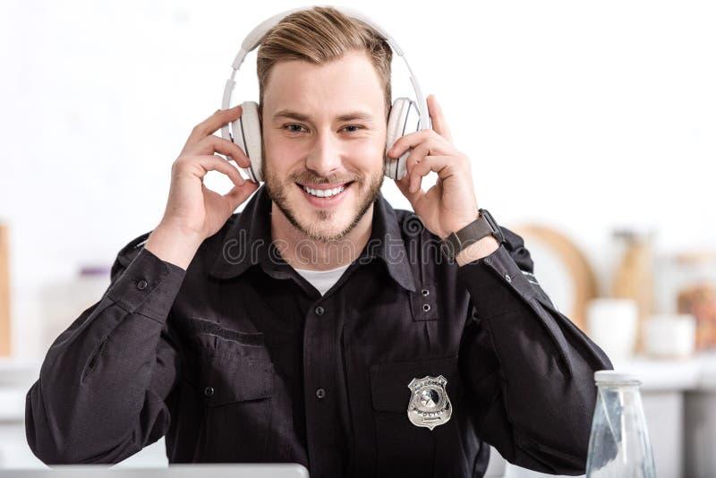 αστυνομικός που χαμογελά και που ακούει τη μουσική με τα ακουστικά στοκ φωτογραφίες