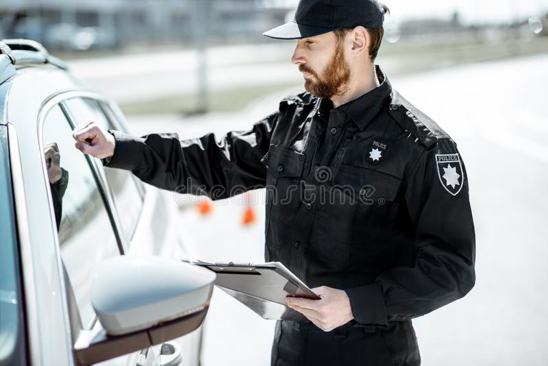 Αστυνομικός που χτυπά στο παράθυρο αυτοκινήτων στοκ φωτογραφία