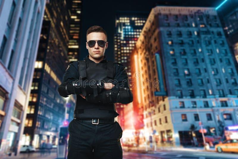 Αστυνομικός στα γυαλιά ηλίου, πόλη νύχτας στοκ φωτογραφίες