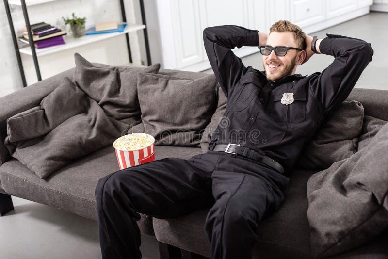 αστυνομικός στα τρισδιάστατα γυαλιά με τα χέρια στην επικεφαλής συνεδρίαση στον καναπέ και στοκ εικόνα με δικαίωμα ελεύθερης χρήσης