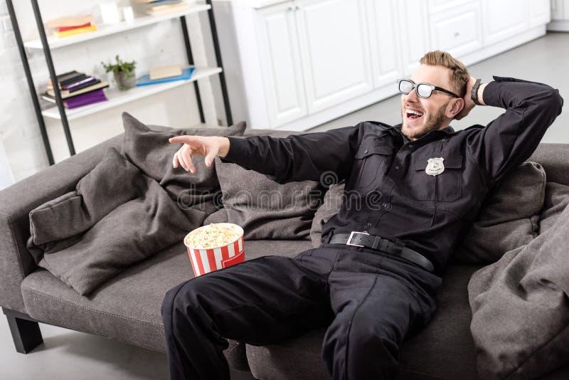 αστυνομικός στα τρισδιάστατα γυαλιά που κάθεται στον καναπέ και στοκ εικόνες