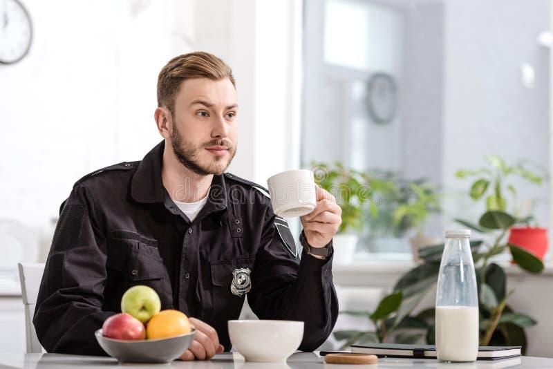 αστυνομικός στη συνεδρίαση κουζινών, το φλυτζάνι εκμετάλλευσης του καυτού καφέ και την κατοχή του προγεύματος στοκ εικόνες με δικαίωμα ελεύθερης χρήσης