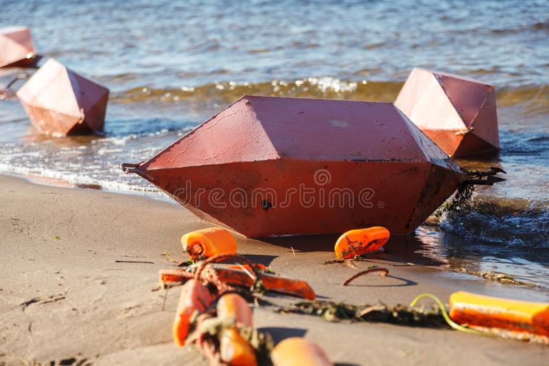 Ασφάλεια στο νερό Διάφοροι μεγάλοι πορτοκαλιοί σημαντήρες βρίσκονται οριζόντια στις αμμώδεις όχθεις του ποταμού στοκ εικόνες