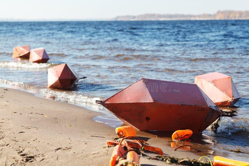 Ασφάλεια στο νερό Διάφοροι μεγάλοι πορτοκαλιοί σημαντήρες βρίσκονται οριζόντια στις αμμώδεις όχθεις του ποταμού στοκ φωτογραφία με δικαίωμα ελεύθερης χρήσης