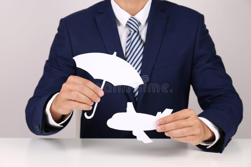 Ασφαλιστικός πράκτορας που καλύπτει το αεροπλάνο εγγράφου με τη διακοπή ομπρελών στον πίνακα, κινηματογράφηση σε πρώτο πλάνο στοκ φωτογραφία με δικαίωμα ελεύθερης χρήσης