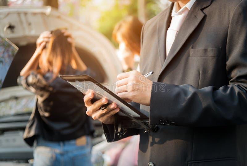 Ασφαλιστικός πράκτορας που εξετάζει το αυτοκίνητο μετά από το ατύχημα στοκ εικόνα