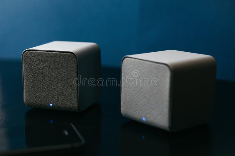 Ασύρματοι ομιλητές και ένα τηλέφωνο κυττάρων δίπλα σε τους σε ένα σκοτεινό υπόβαθρο r στοκ φωτογραφία