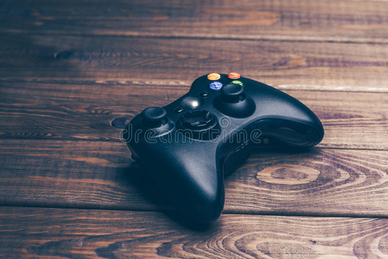 Ασύρματος ελεγκτής gamepad ή παιχνιδιών για το τυχερό παιχνίδι κονσολών στον αγροτικό ξύλινο πίνακα στοκ φωτογραφία με δικαίωμα ελεύθερης χρήσης