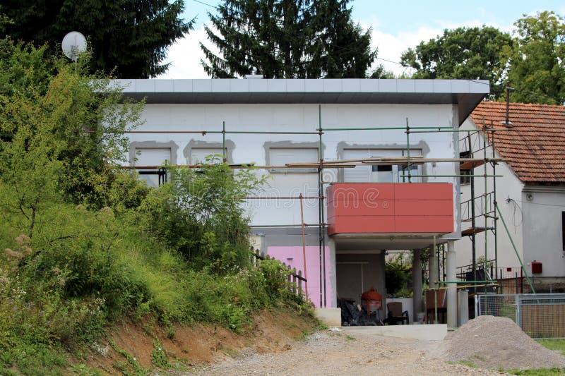Ατελές μικρό προαστιακό οικογενειακό σπίτι που περιβάλλεται με τα υλικά σκαλωσιάς και την πυκνή βλάστηση στοκ εικόνες με δικαίωμα ελεύθερης χρήσης
