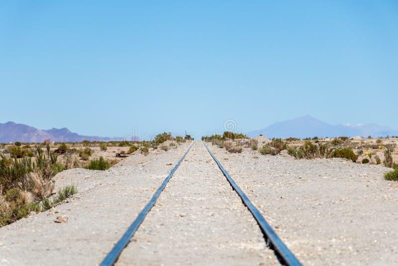 Ατελείωτος δρόμος ραγών στο νεκροταφείο ατμομηχανών ατμού, αλατισμένο επίπεδο Uyuni, Βολιβία στοκ εικόνες