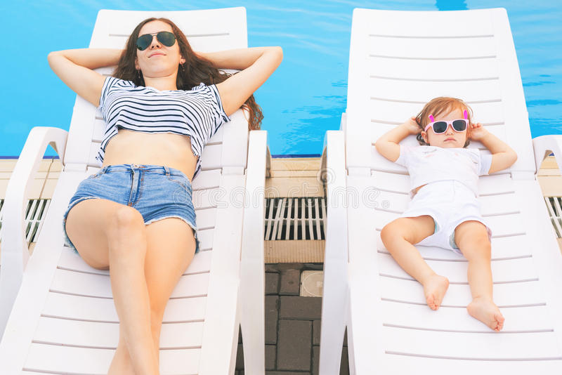 Ατελείωτο καλοκαίρι! Η χαριτωμένη χαλάρωση μωρών και μητέρων στοκ εικόνα