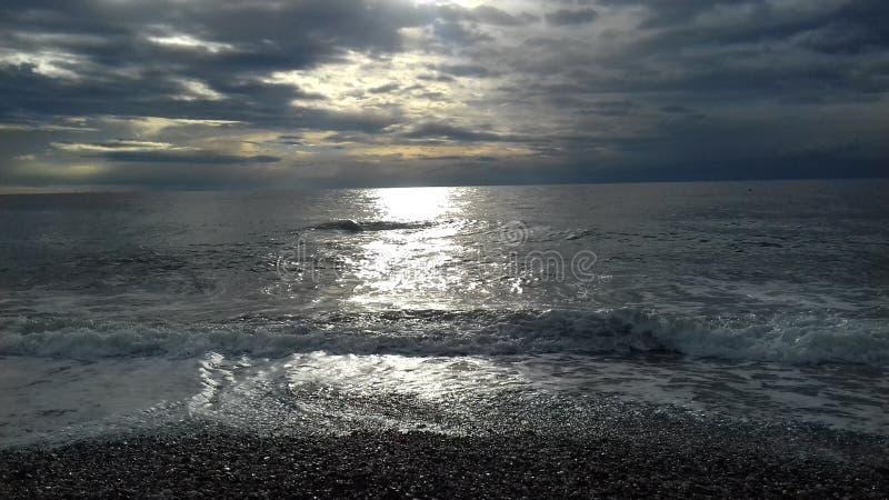 Ατμοσφαιρικός νεφελώδης ουρανός με τον ήλιο στη θάλασσα στοκ φωτογραφία