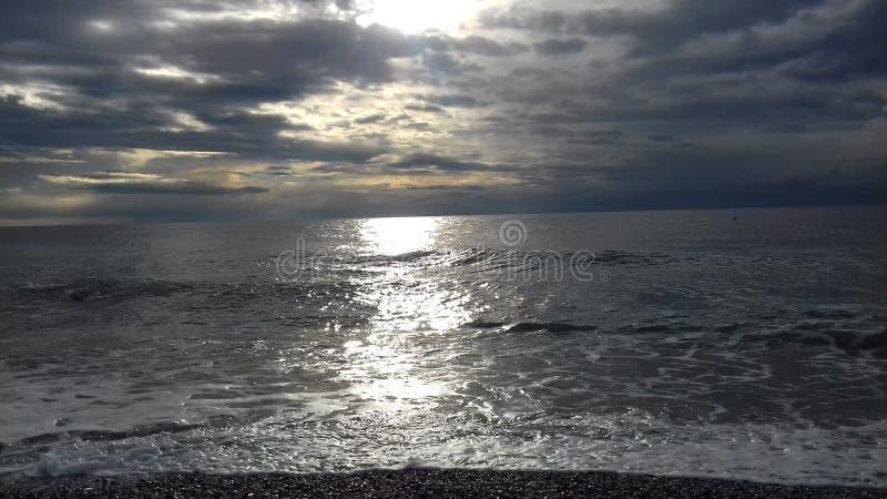 Ατμοσφαιρικός νεφελώδης ουρανός με τον ήλιο στον ήρεμο ωκεανό στοκ εικόνες