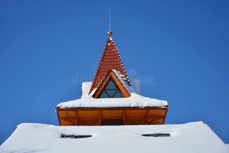 Αττικό παράθυρο της τριγωνικής μορφής στη χιονισμένη στέγη στο backgro στοκ φωτογραφίες