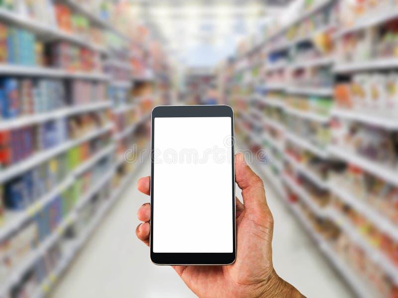 Ατόμων ` s χεριών κινητό τηλέφωνο οθόνης εκμετάλλευσης κενό άσπρο στο θολωμένο υπόβαθρο υπεραγορών στοκ φωτογραφίες
