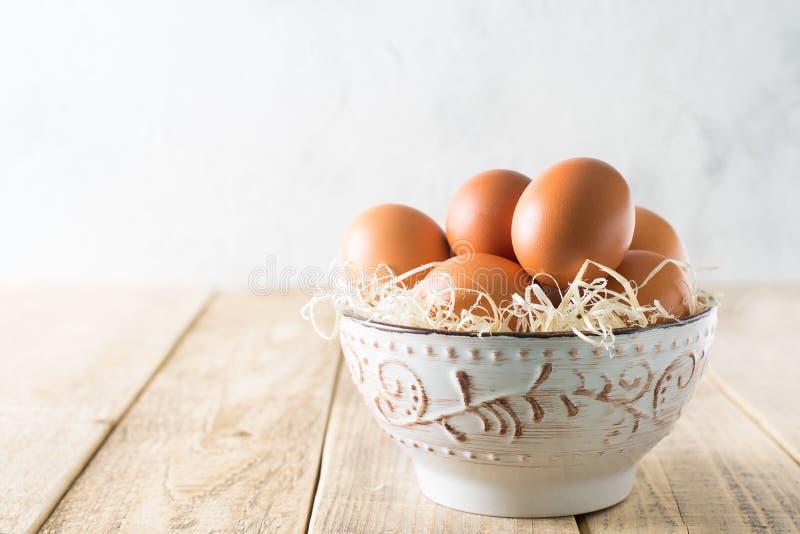 Αυγά κοτόπουλου στο κύπελλο στον ξύλινο πίνακα, αγροτικός, θέμα Πάσχας στοκ φωτογραφίες με δικαίωμα ελεύθερης χρήσης
