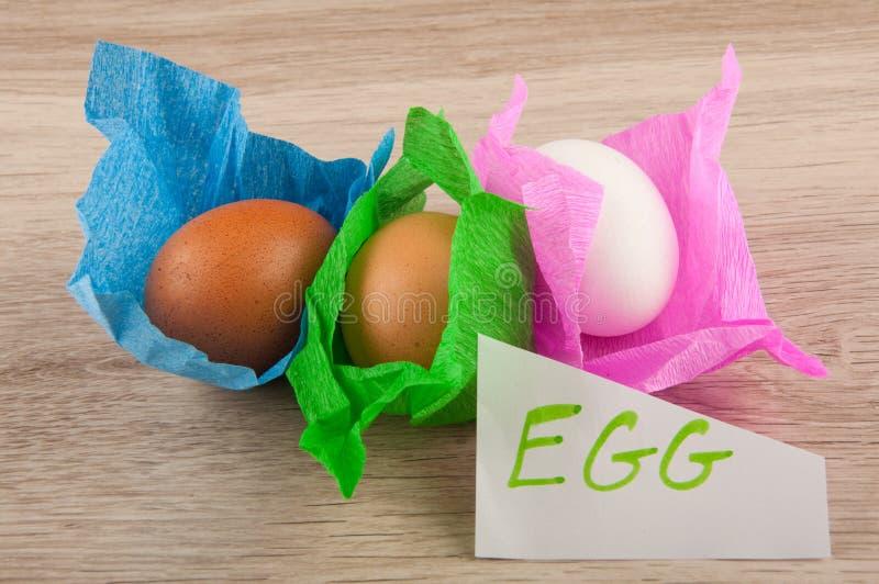 Αυγά κοτόπουλου στο έγγραφο που βάζει στον ξύλινο πίνακα στοκ εικόνες