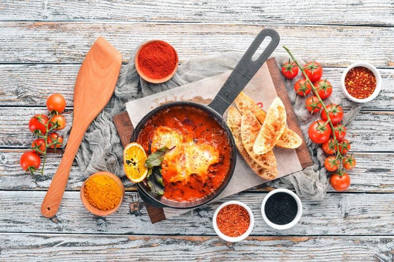 Αυγά με τις ντομάτες και ψωμί φρυγανιάς σε ένα τηγανίζοντας τηγάνι Τοπ άποψη Shakshuka r στοκ φωτογραφία με δικαίωμα ελεύθερης χρήσης