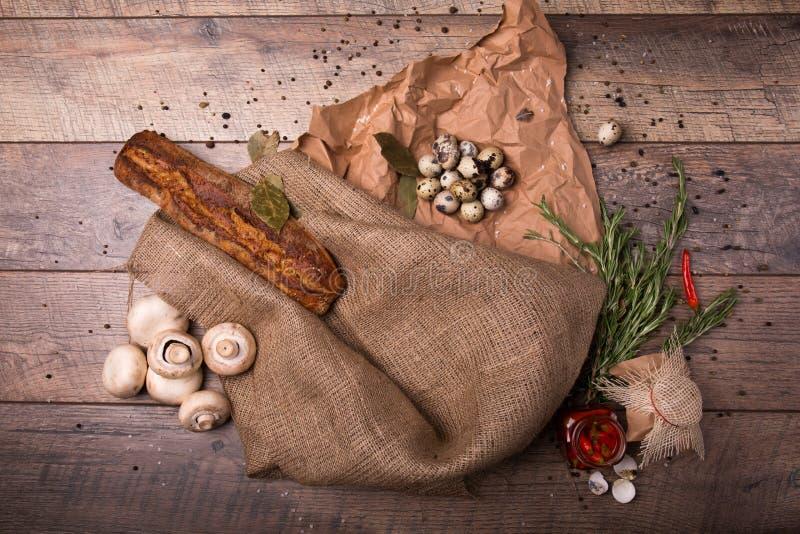Αυγά ορτυκιών, μανιτάρια, καρυκεύματα σε ένα ξύλινο υπόβαθρο Τραγανά baguette και αυγά Μια σύνθεση των αγροτικών συστατικών στοκ εικόνες