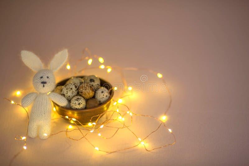 Αυγά ορτυκιών σε ένα ξύλινο πιάτο και ένα λαγουδάκι παιχνιδιών Πάσχας σε ένα ρόδινο υπόβαθρο στοκ φωτογραφία με δικαίωμα ελεύθερης χρήσης