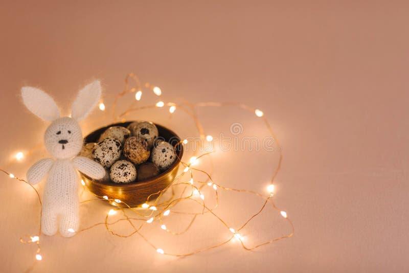 Αυγά ορτυκιών σε ένα ξύλινο πιάτο και ένα λαγουδάκι παιχνιδιών Πάσχας σε ένα ρόδινο υπόβαθρο στοκ φωτογραφίες με δικαίωμα ελεύθερης χρήσης