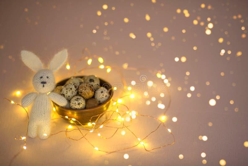 Αυγά ορτυκιών σε ένα ξύλινο πιάτο και ένα λαγουδάκι παιχνιδιών Πάσχας σε ένα ρόδινο υπόβαθρο στοκ εικόνες