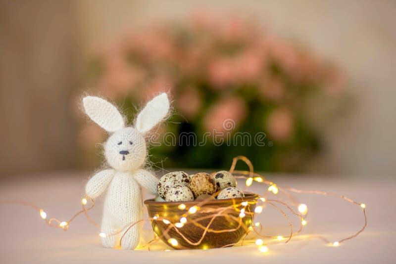 Αυγά ορτυκιών σε ένα ξύλινο πιάτο και ένα λαγουδάκι παιχνιδιών Πάσχας σε ένα ρόδινο υπόβαθρο στοκ εικόνα με δικαίωμα ελεύθερης χρήσης