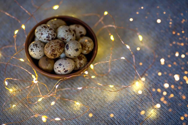 Αυγά ορτυκιών σε ένα ξύλινο πιάτο σε ένα μπλε υπόβαθρο με τα χρυσά φω'τα στοκ φωτογραφίες με δικαίωμα ελεύθερης χρήσης
