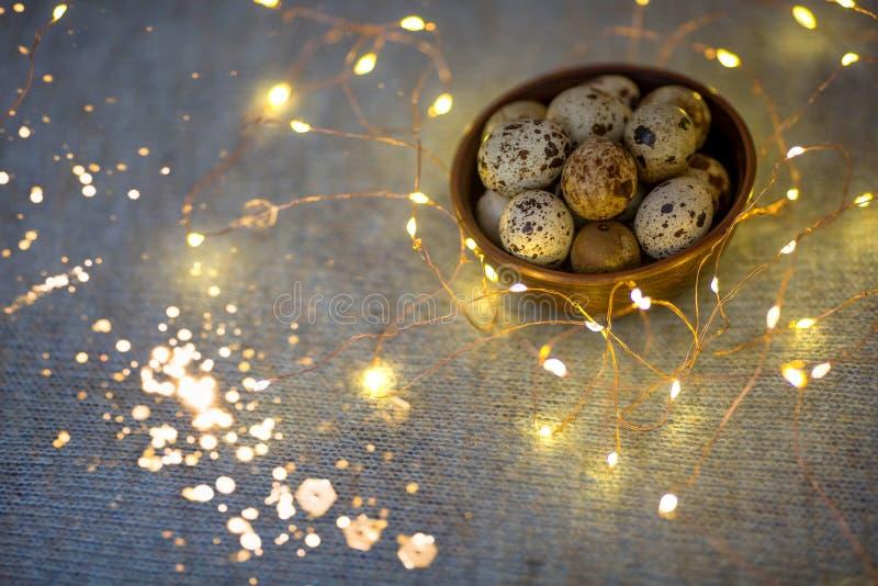 Αυγά ορτυκιών σε ένα ξύλινο πιάτο σε ένα μπλε υπόβαθρο με τα χρυσά φω'τα στοκ φωτογραφία