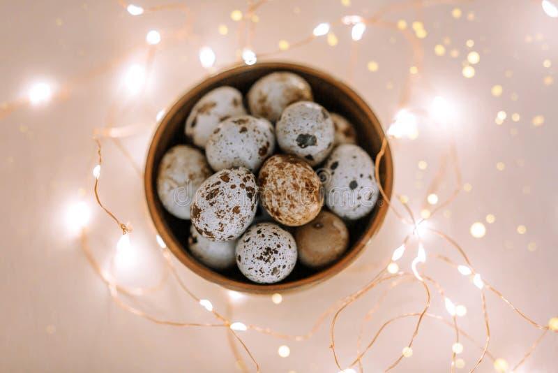 Αυγά ορτυκιών σε ένα ξύλινο πιάτο σε ένα ρόδινο υπόβαθρο με τα χρυσά φω'τα στοκ φωτογραφία με δικαίωμα ελεύθερης χρήσης