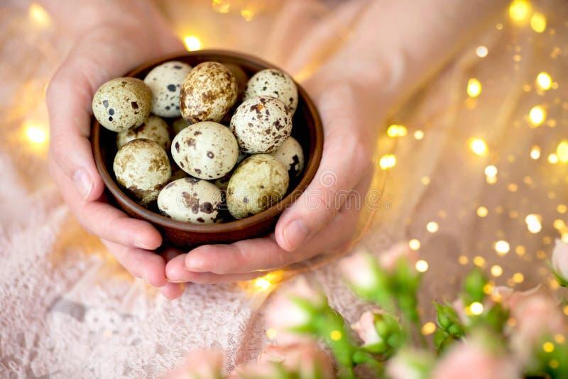 Αυγά ορτυκιών σε ένα ξύλινο πιάτο στα χέρια ενός κοριτσιού σε ένα ρόδινο υπόβαθρο στοκ φωτογραφία με δικαίωμα ελεύθερης χρήσης