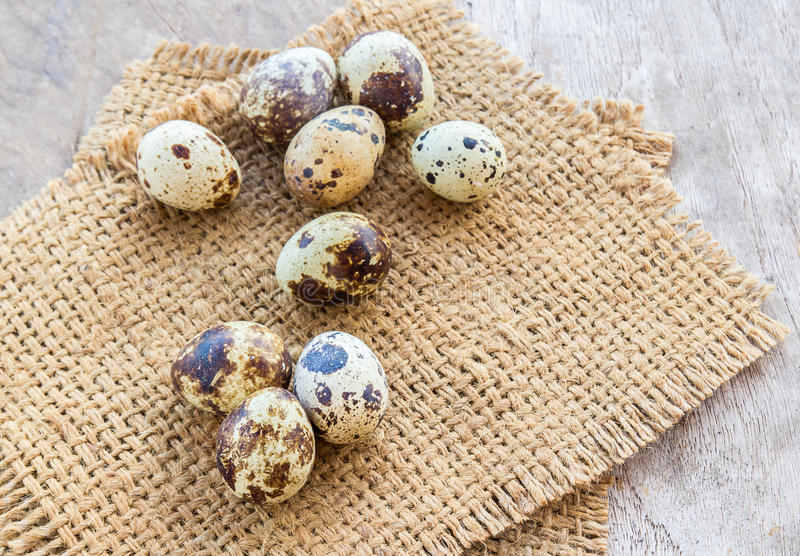 Αυγά ορτυκιών burlap στο σάκο σε έναν ξύλινο πίνακα στοκ φωτογραφίες
