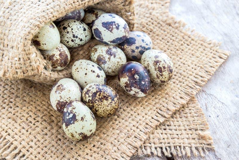 Αυγά ορτυκιών burlap στο σάκο σε έναν ξύλινο πίνακα στοκ φωτογραφία