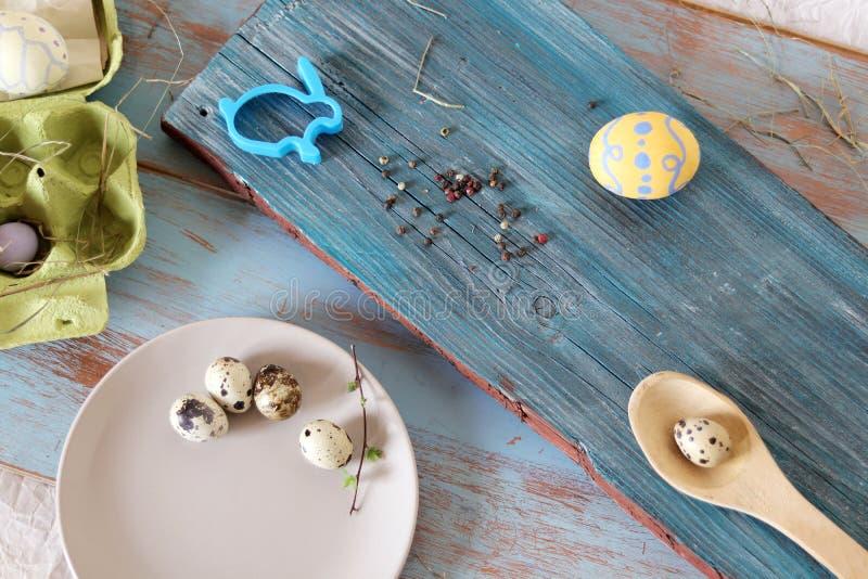 Αυγά, ορτύκια, ντεκόρ Πάσχας σε έναν μπλε ξύλινο πίνακα στοκ φωτογραφία