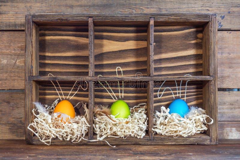 Αυγά Πάσχας με τα αυτιά λαγουδάκι στις φωλιές στοκ εικόνες