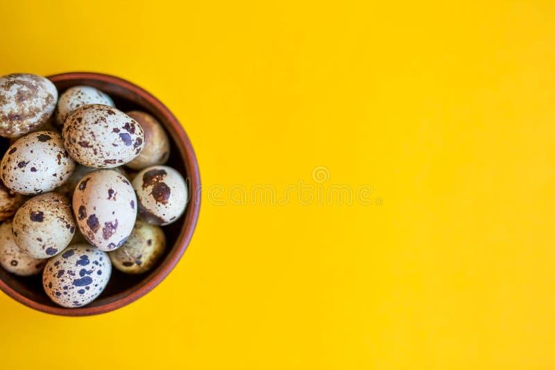 Αυγά Πάσχας ορτυκιών σε ένα ξύλινο πιάτο σε ένα κίτρινο υπόβαθρο στοκ φωτογραφία με δικαίωμα ελεύθερης χρήσης