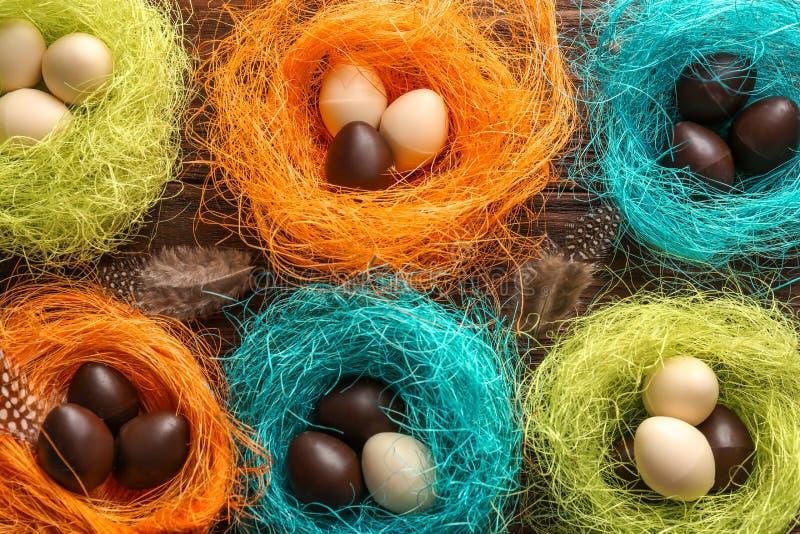 Αυγά Πάσχας σοκολάτας στις ζωηρόχρωμες διακοσμητικές φωλιές στο ξύλινο υπόβαθρο, τοπ άποψη στοκ φωτογραφίες