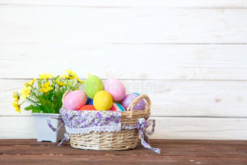 Αυγά Πάσχας στο καλάθι με τα κίτρινα λουλούδια στον καφετή πίνακα στο άσπρο αγροτικό ξύλινο υπόβαθρο στοκ εικόνες