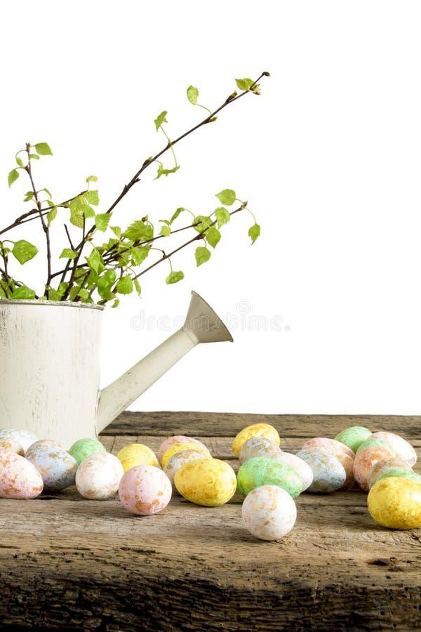 Αυγά Πάσχας στο ξύλινο δοχείο πινάκων και ποτίσματος με τους κλάδους του δέντρου που απομονώνεται στο άσπρο υπόβαθρο στοκ εικόνες με δικαίωμα ελεύθερης χρήσης