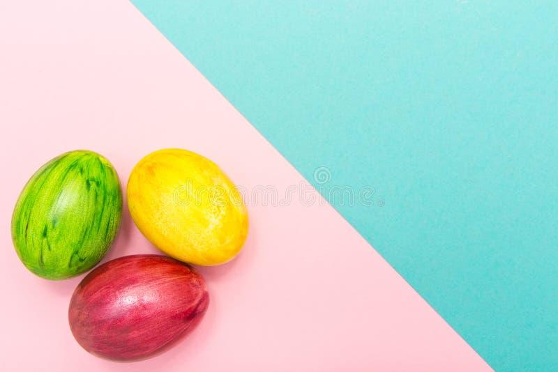 Αυγά Πάσχας στο τυρκουάζ και ρόδινο γεωμετρικό υπόβαθρο Πράσινο, κίτρινο και κόκκινο χειροποίητο νέο ύφος αυγών του χρωματισμού σ στοκ εικόνες