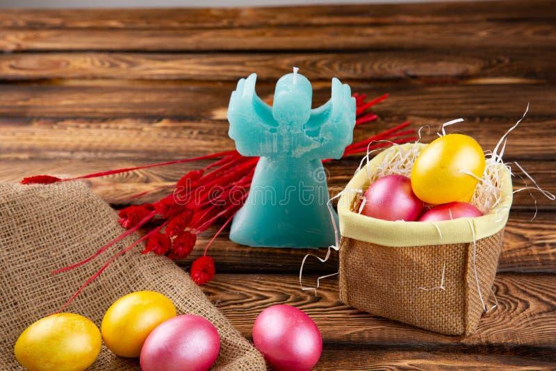 Αυγά Πάσχας sackcloth και ξύλινο ένα υπόβαθρο Ευτυχή φωτεινά πολύχρωμα λαμπρά Πάσχα αυγά Πάσχας Υπόβαθρο με τα αυγά Πάσχας στοκ εικόνα