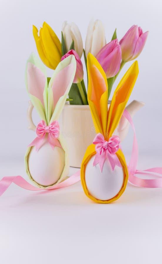 Αυγά πετσετών λαγουδάκι για Πάσχα και λουλούδια στο άσπρο υπόβαθρο στοκ εικόνες με δικαίωμα ελεύθερης χρήσης