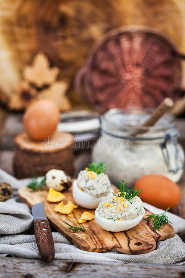 Αυγά που γεμίζονται με το κρεμώδες πατέ ρεγγών στο ξύλινο αγροτικό backgroun στοκ εικόνα
