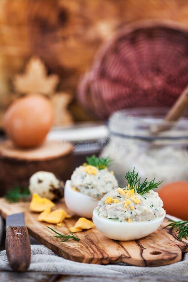 Αυγά που γεμίζονται με το κρεμώδες πατέ ρεγγών στο ξύλινο αγροτικό backgroun στοκ φωτογραφία