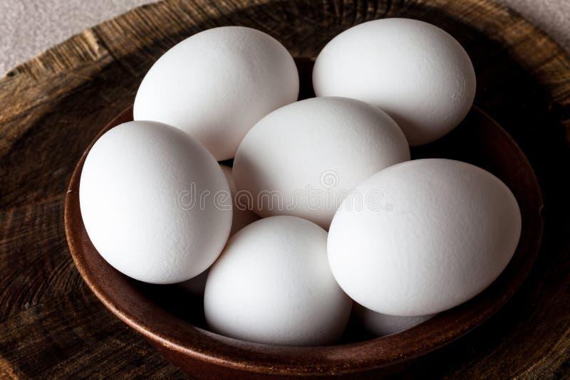Αυγά σε ένα κύπελλο στην τέμνουσα κινηματογράφηση σε πρώτο πλάνο πινάκων άνωθεν στοκ φωτογραφίες