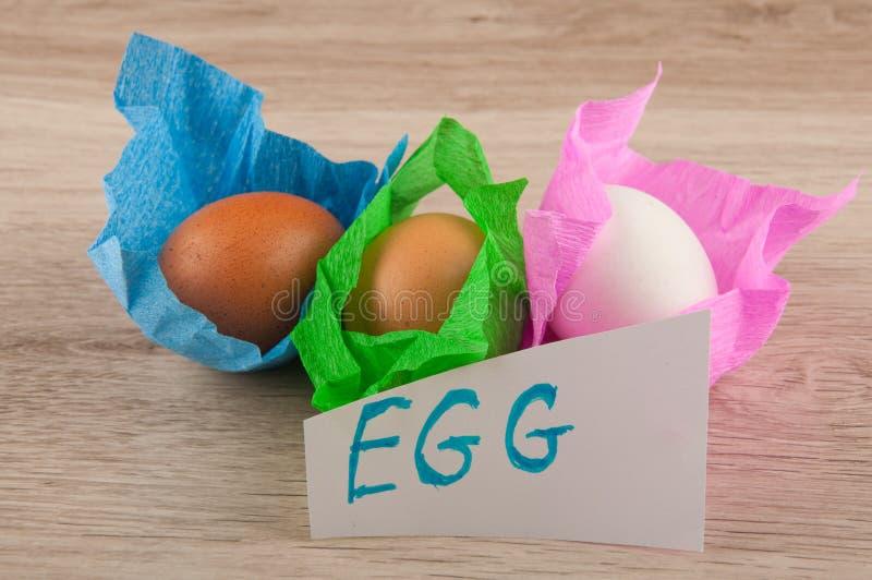 Αυγά τίτλου και κοτόπουλου στο έγγραφο που βάζει στον ξύλινο πίνακα στοκ φωτογραφία με δικαίωμα ελεύθερης χρήσης