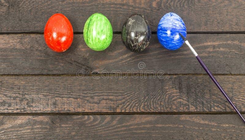 Αυγά χρωματισμού με τη βούρτσα για το eastertime στο σπίτι στοκ εικόνες