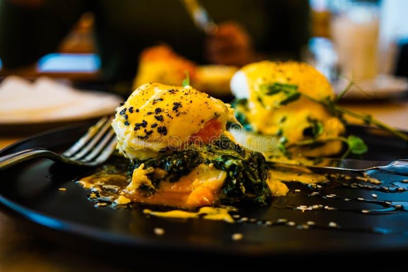 Αυγά Florentine στο μαύρο πιάτο με το δίκρανο στοκ φωτογραφίες