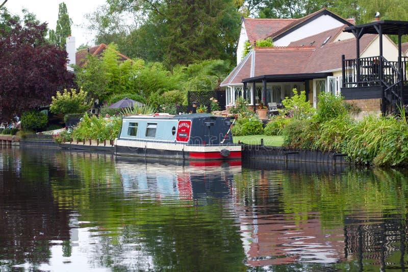 3 Αυγούστου 2019 - Harefield, Αγγλία: Κανάλι με το σπίτι και βάρκα που απεικονίζεται στο νερό στοκ εικόνες